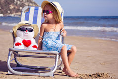 A child sits on a deck chair with a toy Stock Photo