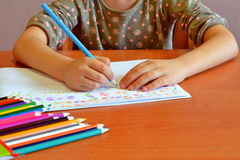 Child sits and draws flowers Stock Photo