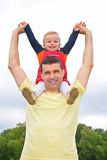 Child sits at father on shoulders with lifted hand. Little child sits at father on shoulders with lifted hands outdoors royalty free stock image