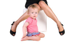 Child sits between female legs in shoes Royalty Free Stock Images