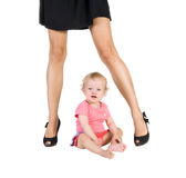 Child sits between female legs in shoes Royalty Free Stock Photography