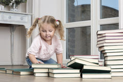 The child sits on the floor, rearranging books. A girl surrounded by stacks of books Royalty Free Stock Image