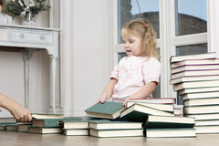 The child sits on the floor, rearranging books. Mom helps daughter to disassemble the book Royalty Free Stock Photo