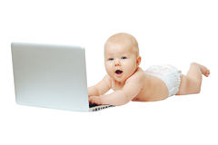 Child sits in front of a laptop and push buttons. Happy little baby lying naked in front of a silver laptop and presses a button Stock Photo