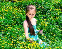 The child sits on a glade with flowers Stock Photo