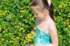 The child sits on a glade and holds flowers Royalty Free Stock Photos