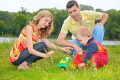 Child sits on grass with parents and plays with to Stock Photo