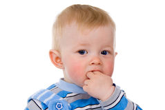 The child sits, hand in the mouth Stock Images