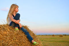 The child sits on a hay bale Royalty Free Stock Image