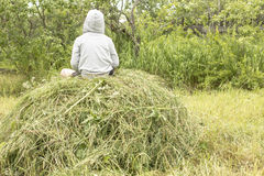 Child sits on haystack and enjoy the warm a summer eveningon the Royalty Free Stock Photo