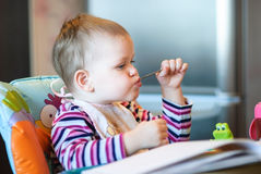 The child sits in a high chair and holding a spoon in his mouth Royalty Free Stock Image