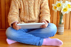 Child sits holding a tablet in hands. Vase of daffodils. Wooden background Royalty Free Stock Photo