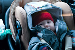 Child sits looking in safety seat. The child sits looking in car safety seat Stock Image