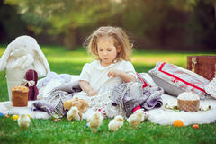 Child sits on a meadow around easter decoration Stock Photo