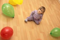 Child sits in the middle of many colorful balloons Stock Image