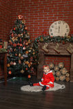 Child sits near a Christmas tree. Baby girl dressed as Santa Claus sits near a Christmas tree Royalty Free Stock Images
