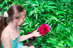 The child sits near a flower Royalty Free Stock Photos