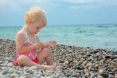 Child sits on pebble beach Royalty Free Stock Photo