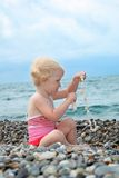 Child sits on pebble beach Royalty Free Stock Image