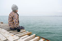 The child sits on the pier and watching the sea in winter Stock Photos
