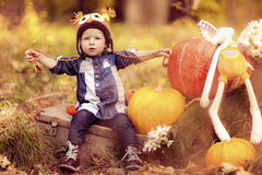 The child sits playing on nature. Royalty Free Stock Image