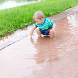 Child sits in a puddle Royalty Free Stock Photos