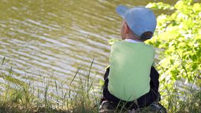 The child sits on the river bank and looks into the river. 4k stock video footage