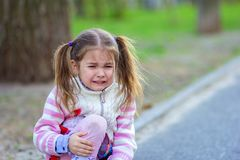 The girl sits on the road and cries, holding a knee. Child sits on the road in the park and cries, holding a knee Royalty Free Stock Photo