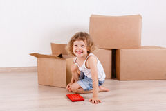 Child sits in a room near the boxes. Stock Photography