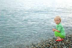 Child sits on seaside Royalty Free Stock Photos
