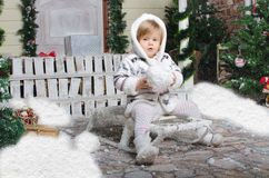 Child sits on sled with snow in hands Royalty Free Stock Photo