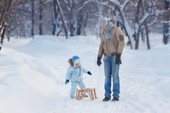 Child sits on the sledge, His Father waits Royalty Free Stock Photos