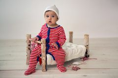 Child sits on a small wooden bed royalty free stock photo