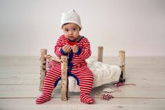 Child sits on a small wooden bed stock photo