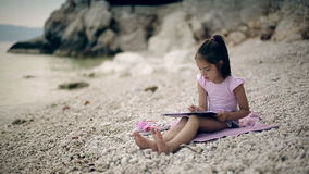 A child sits on a stone near the Adriatic Sea and draws a picture. Medium shot. stock video footage