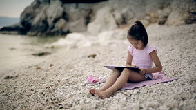 A child sits on a stone near the Adriatic Sea and draws a picture. Medium shot. stock video