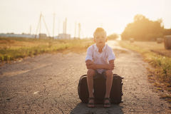 The child sits on a suitcase in the summer sunny day, the travel Royalty Free Stock Photos