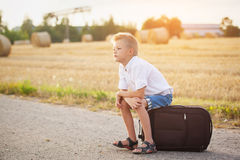 The child sits on a suitcase in the summer sunny day, the travel Royalty Free Stock Photography