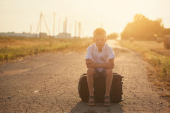 The child sits on a suitcase in the summer sunny day, the travel Royalty Free Stock Images