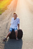 The child sits on a suitcase in the summer sunny day Stock Photo