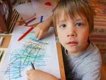 The child sits at the table and draws markers. The child looks i. Nto the lens, and simultaneously draws Stock Image