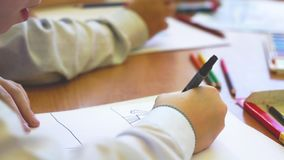 The child sits at a table and draws on paper. stock video footage