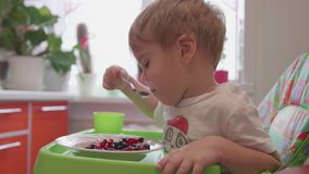 The child sits at the table and eats a spoonful of fresh berries. Useful and healthy food. Child sits at table and eats with a spoon fresh berries stock footage