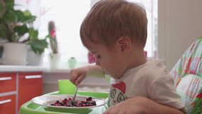 The child sits at the table and eats a spoonful of fresh berries. Useful and healthy food. Child sits at table and eats with a spoon fresh berries stock video footage