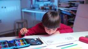 The child sits at a table on which are a pencil case. Pencils, school supplies stock footage