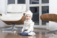 Child sits at the window on the floor. Stock Images