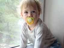 The child sits on the window. The child on the windowsill,next is toy Royalty Free Stock Images