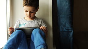 A Child sits on a windowsill with a tablet pc at home stock video footage