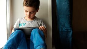 Child sits on a windowsill and uses a digital tablet pc Royalty Free Stock Photography
