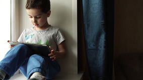 Child sits on a windowsill and uses a digital tablet pc stock footage
